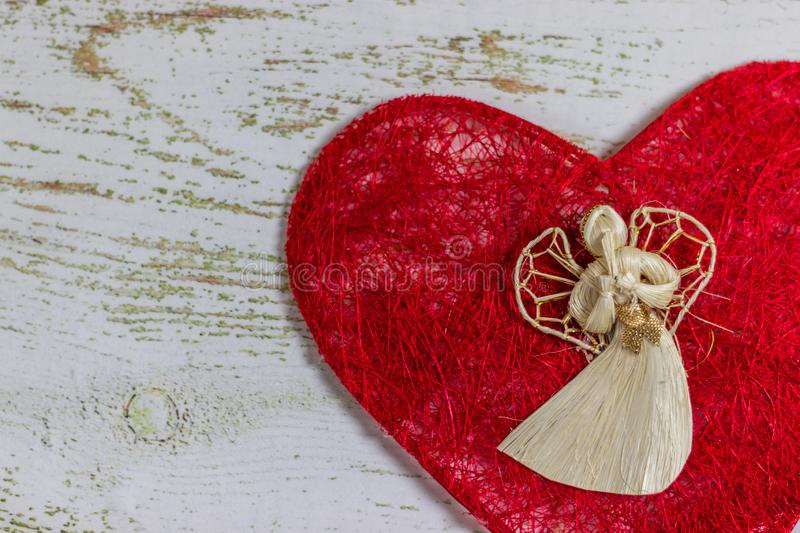 White angel on a red heart. Postcard Happy Valentine`s Day. Light wooden background, place for text, Valentine card. White angel on a red heart. Postcard Happy stock image