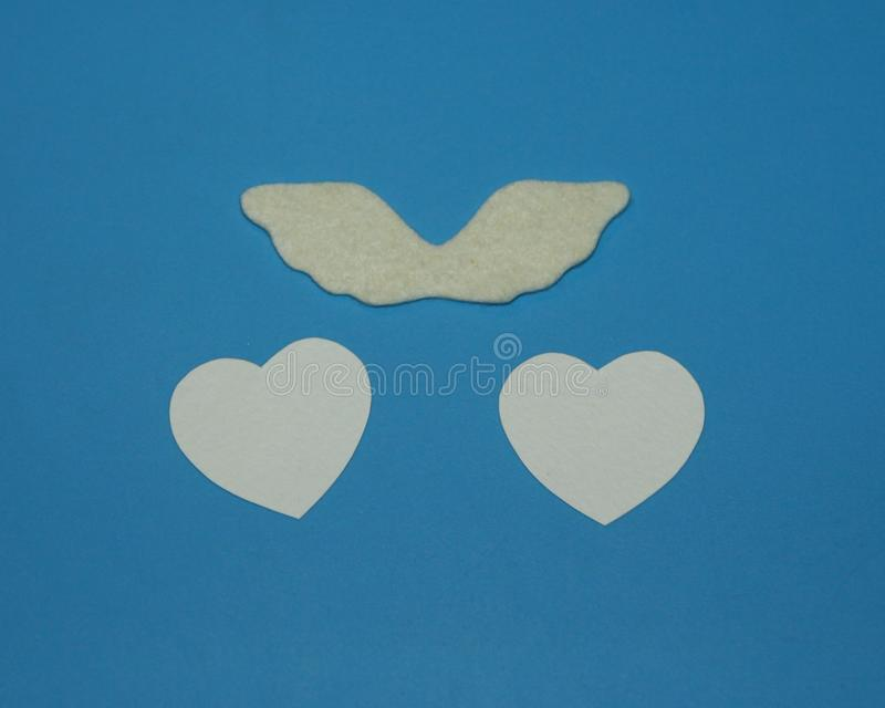 White angel wings of felt and two hearts of white paper on a blue background stock image