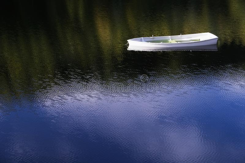 White angelic single lonely boat floating peaceful bliss mindfulness in calm water with blue sky reflection sun shinning brightly royalty free stock images