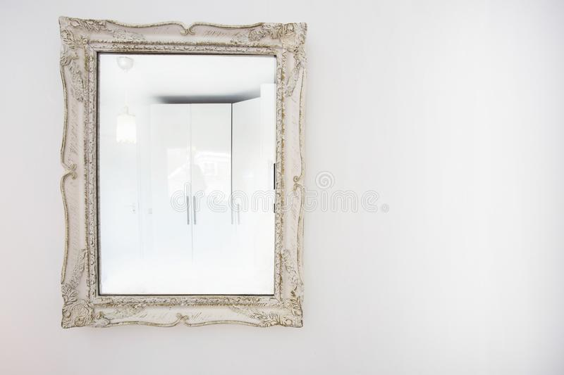 White antique vintage mirror wooden frame on white wall royalty free stock photography