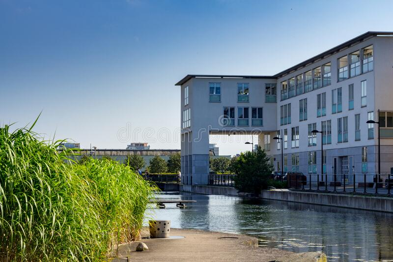 A white apartment building next to a park with reed and water taken on a sunny summer day. Malmö, Sweden - August 9, 2017: A modern apartment building in the stock photography