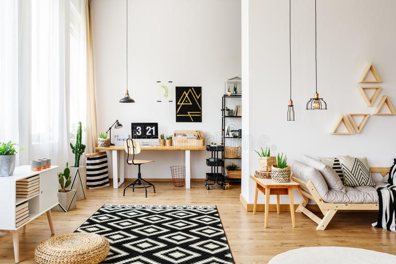 White apartment with creative design. Modern white craft room in open apartment with creative design, triangle shelves, industrial pendant lamps, wooden stock images