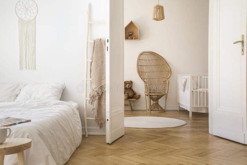 White apartment interior with herringbone parquet, double bed and open door to kid room with peacock chair, white crib. And round rug on the floor royalty free stock image