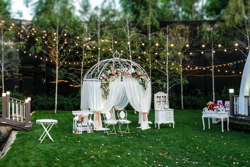 White arch for the wedding ceremony. Decorated with roses, ranunculus and peony. Vintage furniture elements: chair, table, lights bulbs stock photo