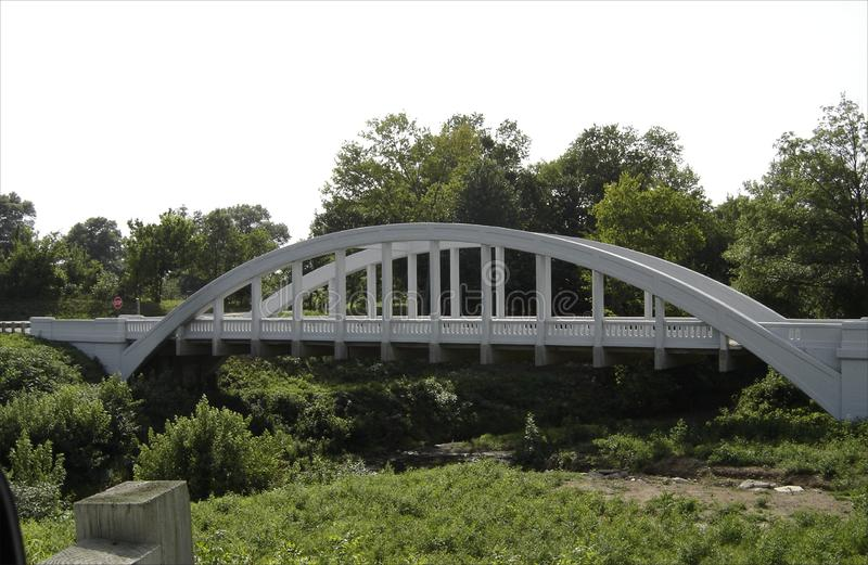White arched bridge on a back road in the midwest. Seen from a newer cross over royalty free stock image