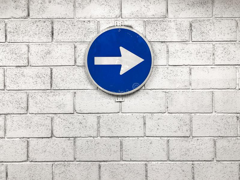 White arrow on blue road sign hanging on wall pointing right dir stock photo