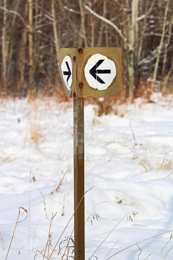 A white arrow direction sign along a hiking path royalty free stock image