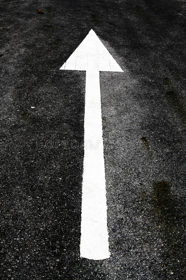 White arrow painted on the road stock images