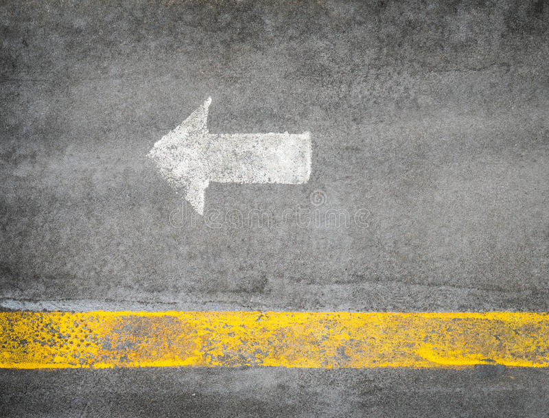 White arrow pointing left on a street stock image