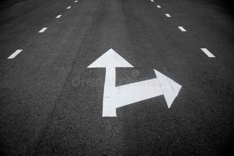 White Arrow Straight Ahead or right Turn Traffic Signs perspective on the road stock photo