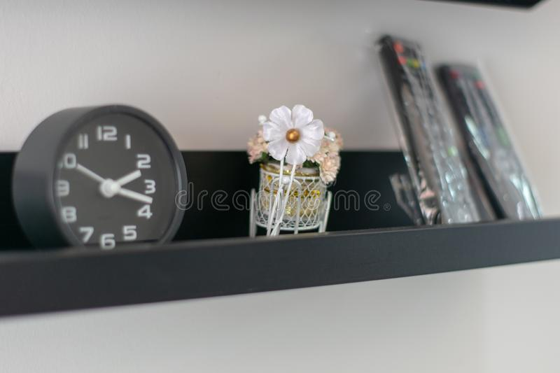 White artificial flowers beside the black alarm clock royalty free stock image