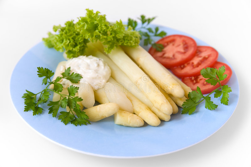 White asparagus. Cooked white asparagus with salad, tomato, parsley and dressing stock image