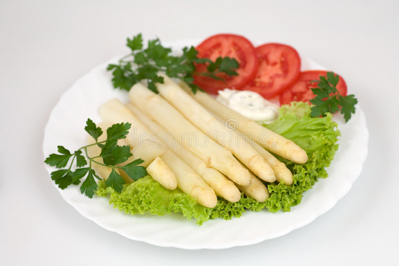 White asparagus. Cooked white asparagus with salad, tomato, parsley and dressing royalty free stock images