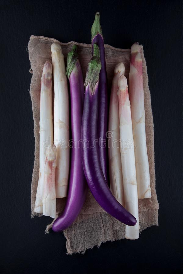 White aspargus and purple violet aubergines decorated with napkin on a kitchen table royalty free stock photos