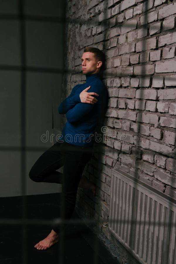 White attractive man in a blue sweater and black pants, barefoot stands near a stone wall, behind bars, a prisoner. White attractive man in a blue sweater and stock image