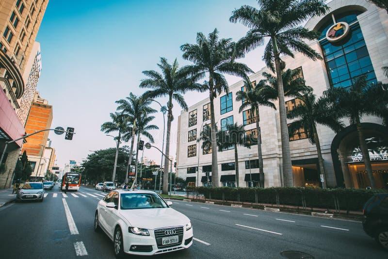 White Audi Sedan on Gray Concrete Road Near Green Trees Surround by Concrete Buildings stock image