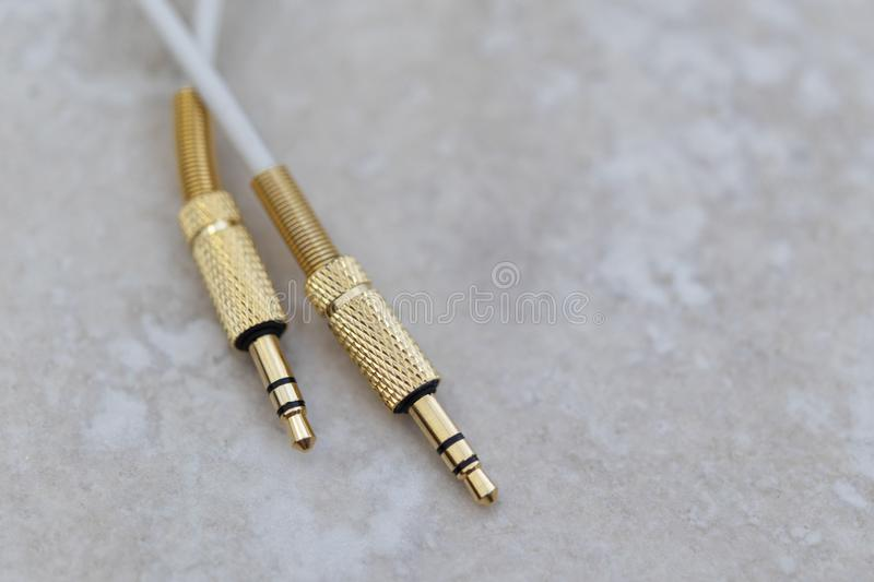 White audio cable with gold metal on a marble background stock image