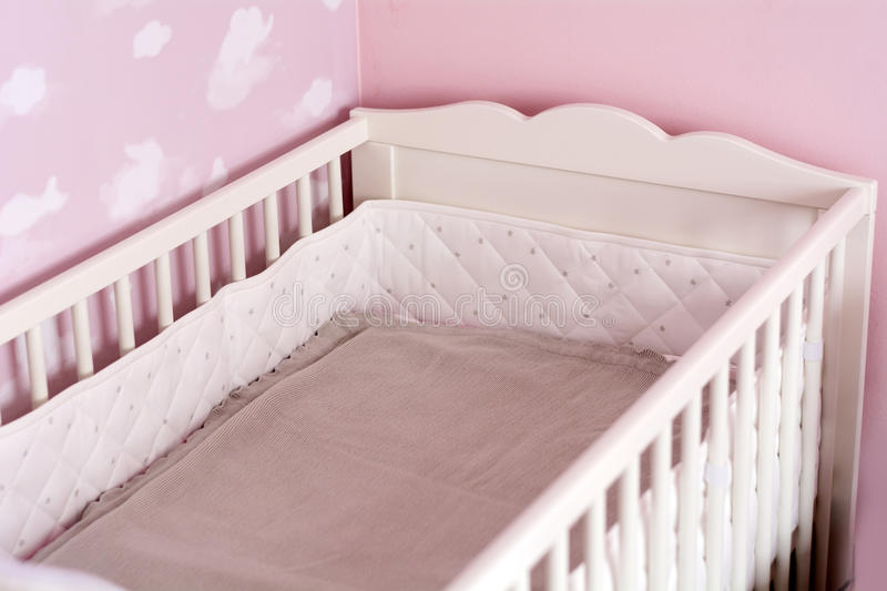 White baby bed. Children`s white bed in a pink room royalty free stock images