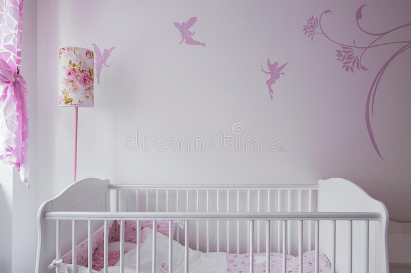 White baby cot. Image of white baby cot with wall decor in background stock photography