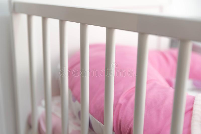 White Baby crib. Detailed shot of a White Baby crib with pink pillow stock image