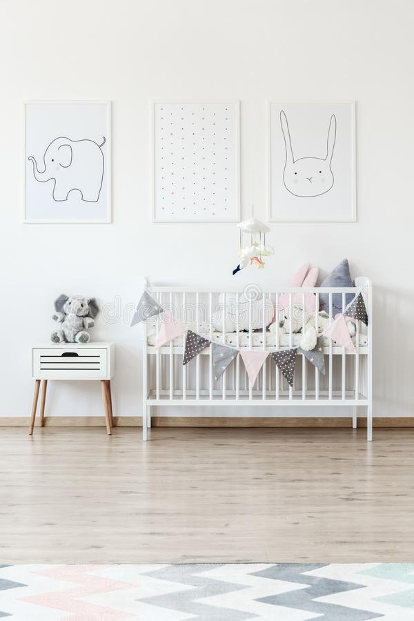 White baby`s bed with banner. Elephant toy on white cabinet next to baby`s bed with banner and pillows against white wall with pictures stock photography
