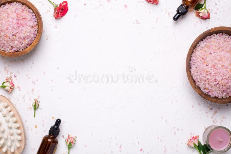 White background with bath salt, massager and natural oil bottles royalty free stock photo