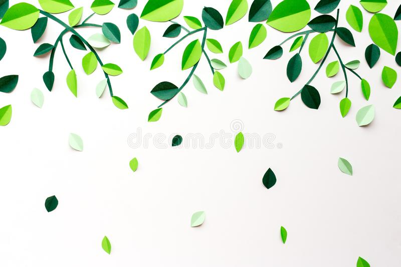 White background with falling green leaves and branches of paper handmade. White background with falling green leaves and branches of paper, decor for postcard stock photography