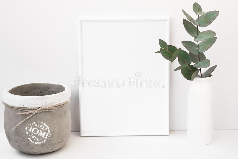 White background frame mockup, green eucalyptus in ceramic vase, cement pot, styled image royalty free stock image