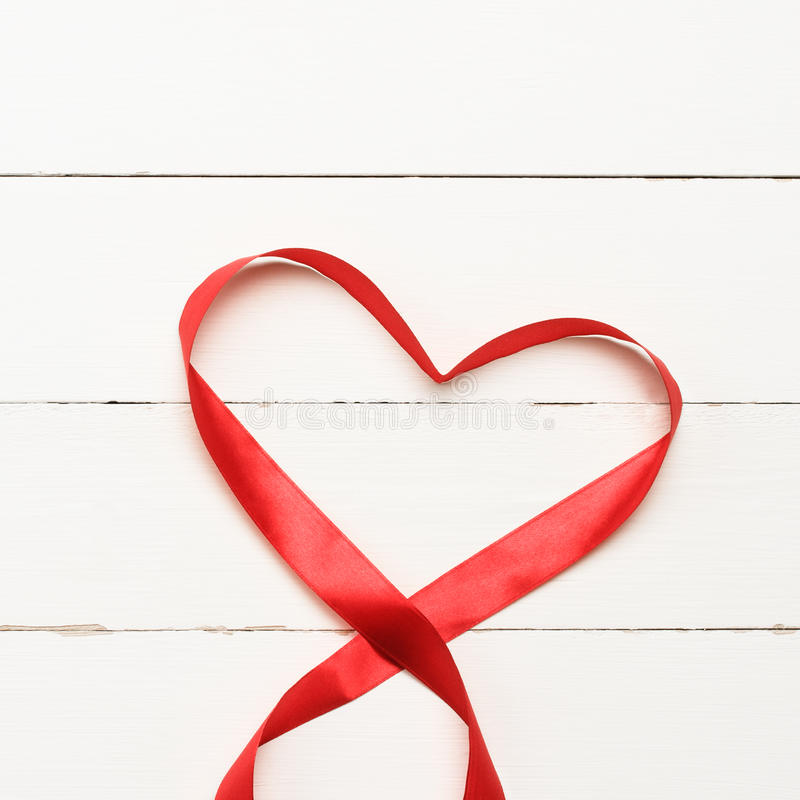 White background with heart shaped ribbon. Red heart shaped ribbon over white wooden background stock images