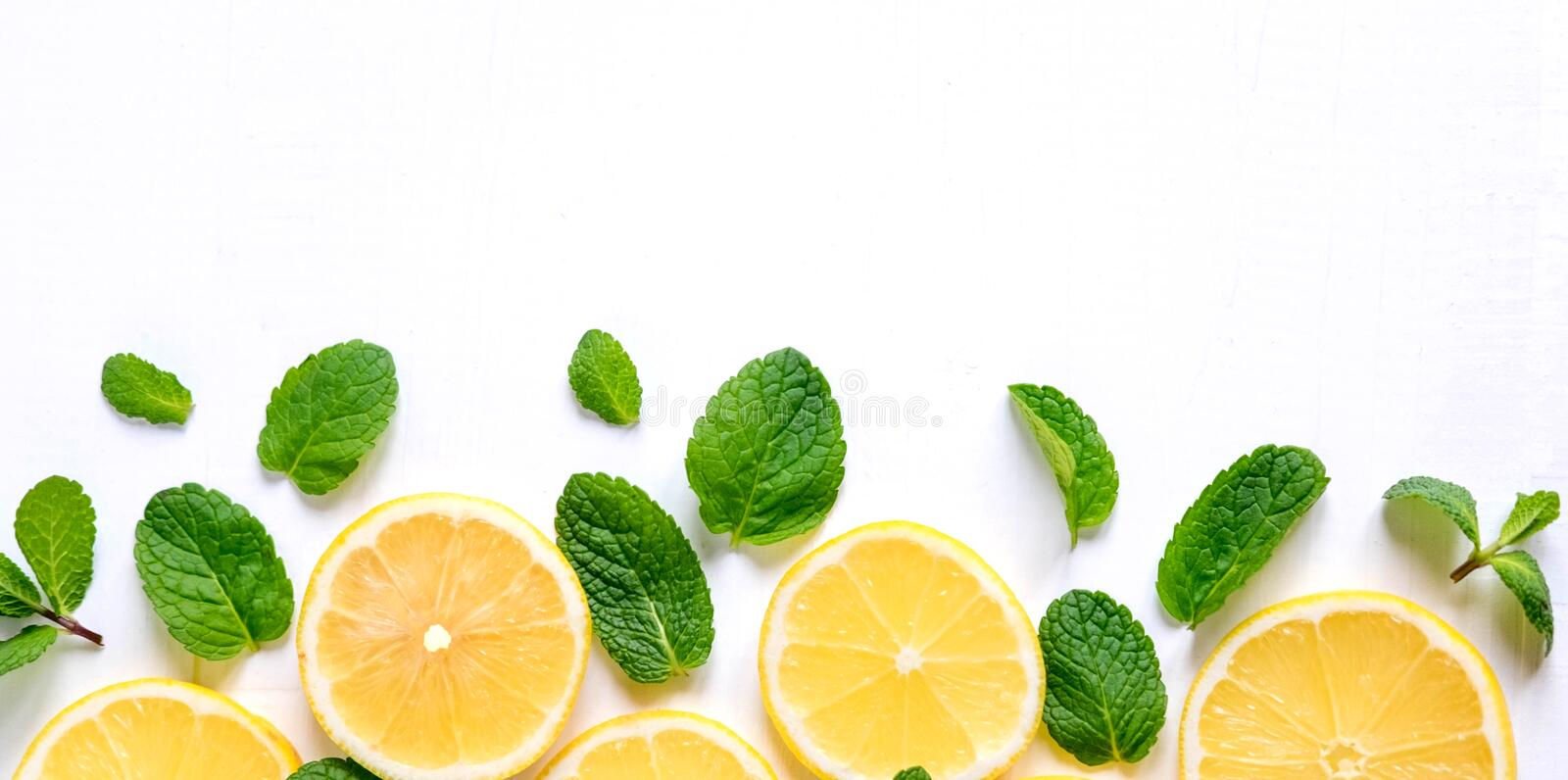 White background with lemon, orange slices and mint. Concept with fresh fruit. Lemon, Orange, Mint. View from above royalty free stock image