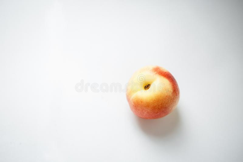Nectarine with yellow and orange sides. On a white background lies a round nectarine with yellow and orange spots on the sides stock photos