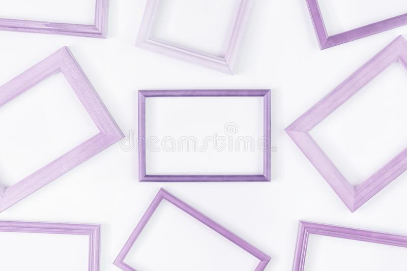 On a white background a lot of lilac empty frames are laid out. Space for text, layout. Unusual concept royalty free stock photos