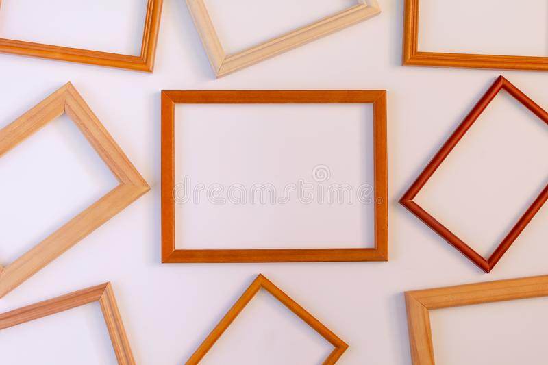 On a white background many wooden empty frames are laid out. Space for text, layout. Unusual concept stock image