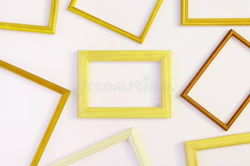 On a white background many yellow empty frames are laid out. Space for text, layout. Unusual concept royalty free stock photography
