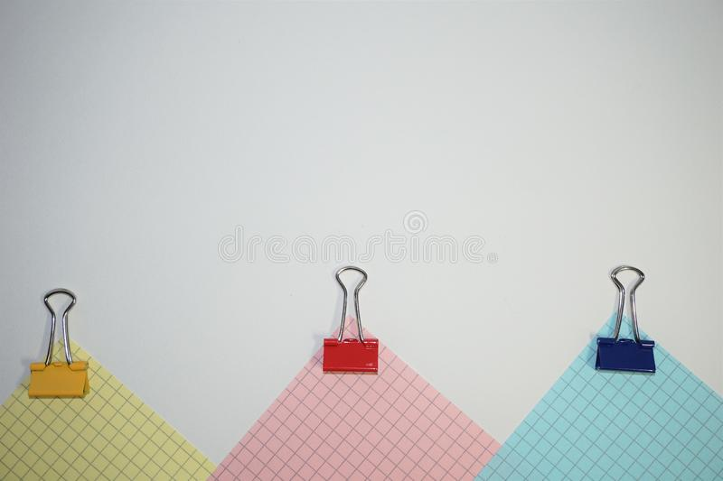White background with multicolored checkered parts. And paper clips. Back to school concept stock images
