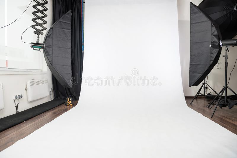 White background in photo studio. Empty photo studio interior with white background and lighting equipment royalty free stock photos