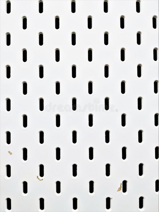 White background with small holes. It serves as a partition for the arrangement of the office workplace. White background with oblong holes. Have a solid stock photography