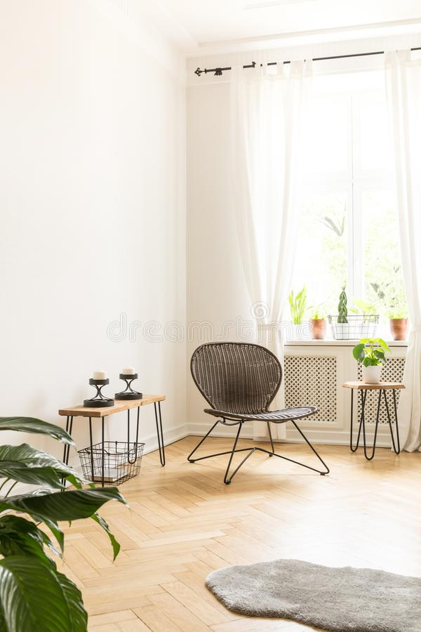 White background wall with empty space in a high ceiling room interior with a rattan and metal chair in the corner and side tables stock photos