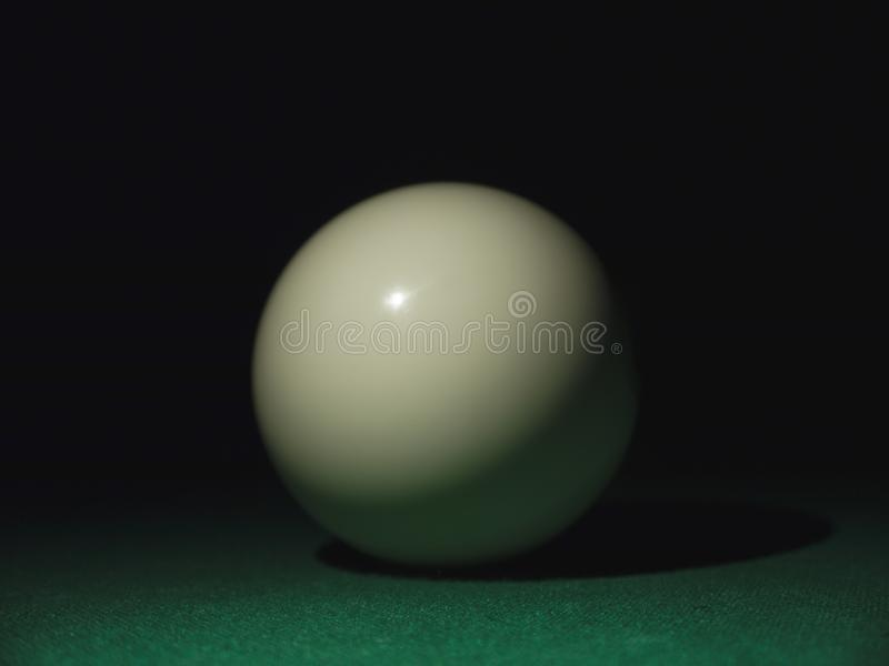 White ball on a billiard table in the dark.  royalty free stock images