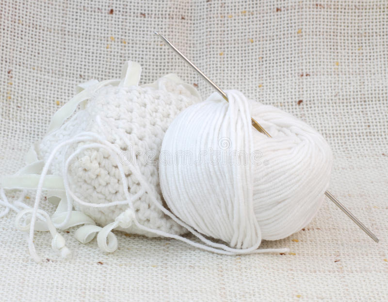 White ball (clew) of yarn and knitting hook royalty free stock photos