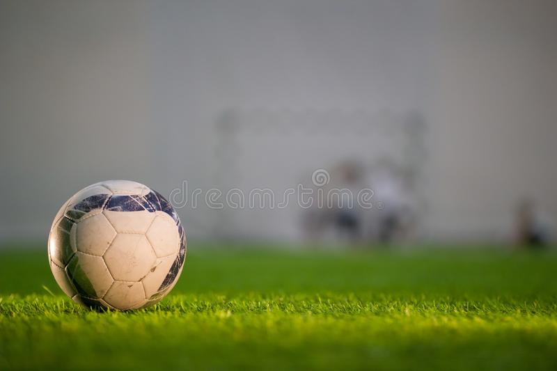 White ball is on the green grass on the football field. On the left side, horizontal stock images