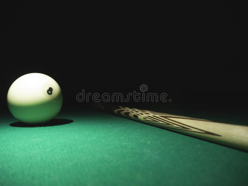 White ball number 8 from russian billiard pyramid and a cue on a table. Black background.  stock images