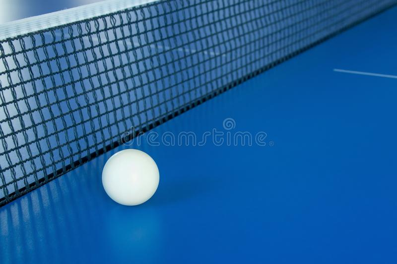 White ball for table tennis lies on a blue table stock photos