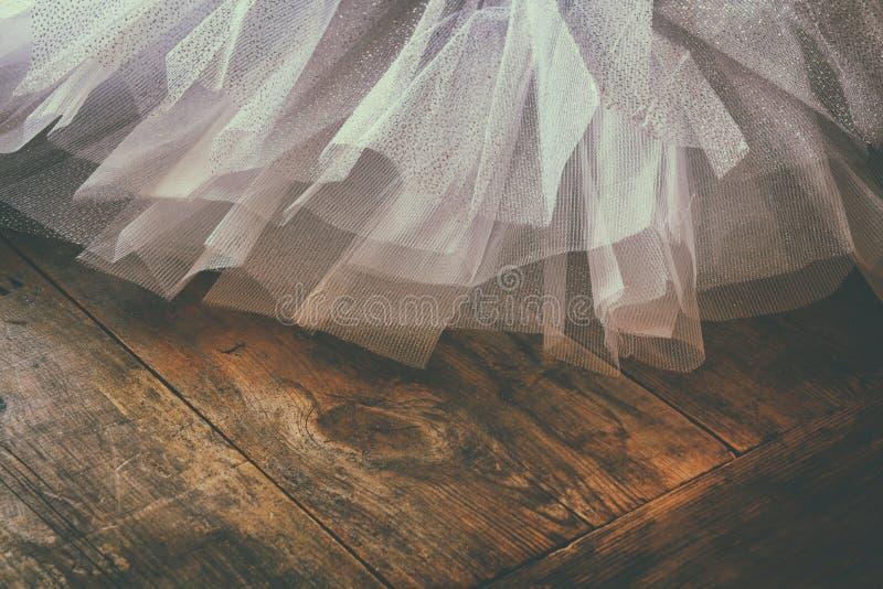 White ballet tutu on wooden floor. Retro filtered royalty free stock image