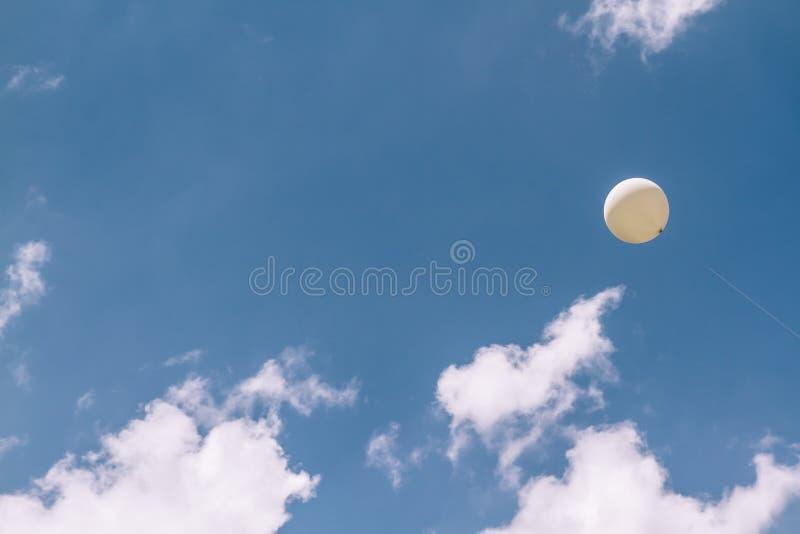 White balloon flying in blue sky stock photos