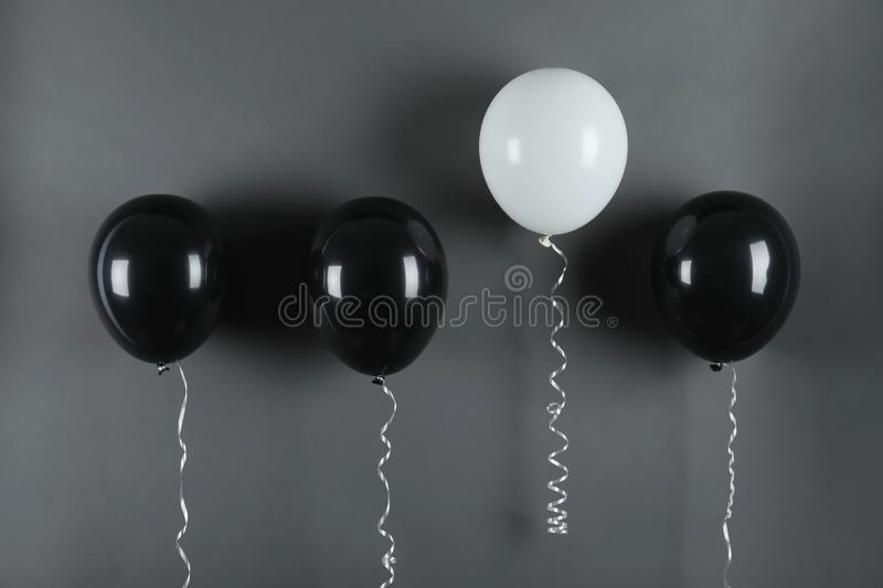 White balloon rising higher than others on black background stock images