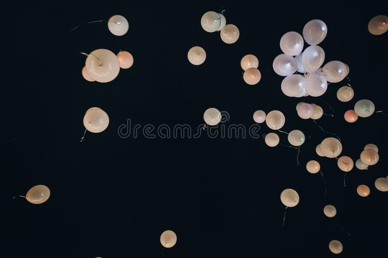 White balloons flying up in the air into night sky after amazing stock images