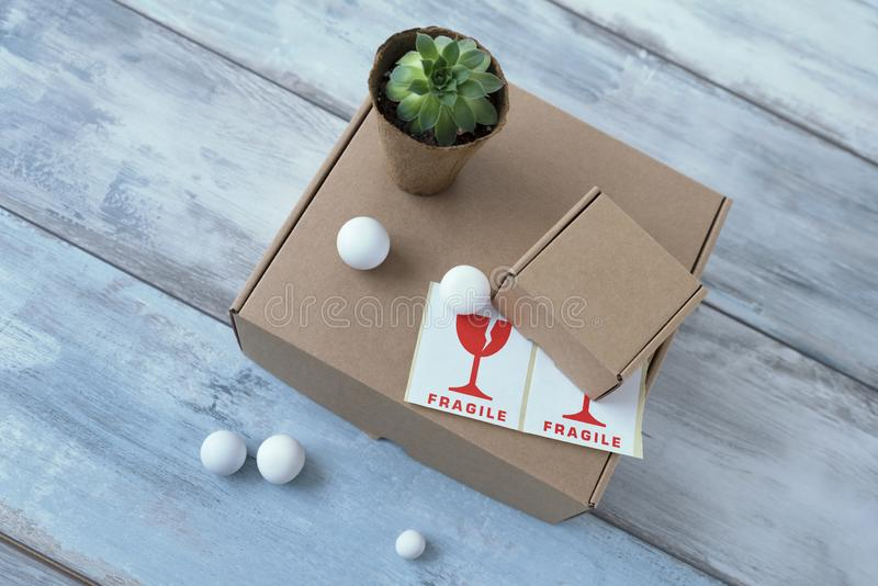 White balls two carton boxes and one pot with green plant and fragile signs on a blue wooden surface royalty free stock photography