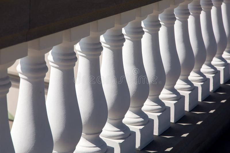 White baluster stone balusters closeup. White baluster stone balusters closeup of an architectural structure lit by sunlight royalty free stock image