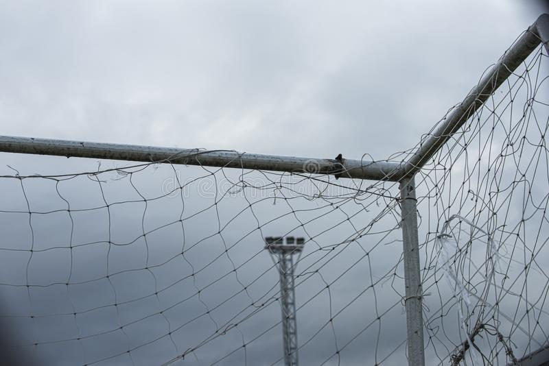 White bar of football goal with broken and messy white net seeing a pylon of stadium lighting ready for the night time. royalty free stock images